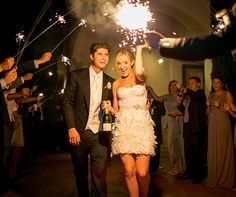With champagne in hand, the bride and groom say goodbye to their guests through a tunnel of sparklers.