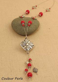 Sautoir léger composé sur un fil gainé argenté . Perle principale en résine  argentée de 3x3 cm ; Perles en verre rondes rouges et perles en métal argenté ; Longueur : 46 - 9799477