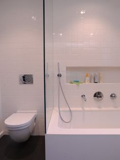 Contemporary bathroom with Ceasarstone tub apron and recessed light valance over custom high gloss lacquer vanity