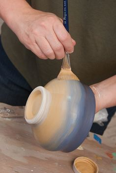 Terri Kern how to apply underglazes.  She uses a red clay and then applies yellow underglaze on top of earthenware.