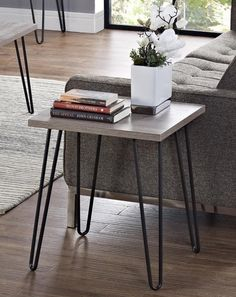 "A gunmetal end table that says, ""I have enough books and flowers to go around."" 