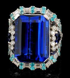 Platinum Weight of Item: 20.26 grams Main Gemstone: Tanzanite Shape: Emerald Cut Weight: 19.23 ct Color: Blue - Violet Adjacent Gemstone: Sapphire Shape: Heart Shape Weight: 1.34 ct Adjacent Gemstone: Paraiba Tourmaline Shape: Round Weight: 0.55 ct Diamonds: Natural Diamonds Shape: Round Brilliant Weight: 1.21cts Clarity Grade: VS Color Grade: E - F