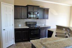 Omega Homes- Dark cabinets with light granite and tile backsplash