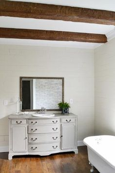 Traci from Beneath My Heart incorporated faux wood beams in her master bathroom to complement a refinished claw-foot tub and an antique dresser turned vanity. You can see the project in its entirety at BeneathMyHeart.net