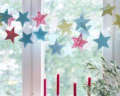 Mit dieser Girlande zaubern Sie sich einen eigenen Sternenhimmel ins Fenster.Für die Girlande brauchen Sie kleine, weiße Pompons (aus dem Bastelladen),...