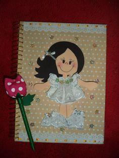 Caderno revestido em tecido de boa qualidade, decorada com boneca em E.V.A. e roupinha de tecido. Caneta/tulipa em tecido