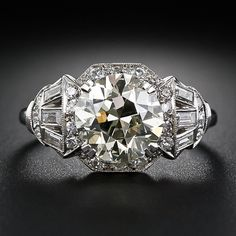 Art Deco ring, superbly handcrafted in platinum, circa 1930s, radiates with a warmly tinted European-cut diamond weighing 3.00 carats. The gorgeous and virtually flawless diamond radiates from a stylized diamond-set octagonal setting which artfully transitions into a shimmering fan of baguette diamonds, creating a spectacular, sophisticated and singular Art Deco engagement ring.