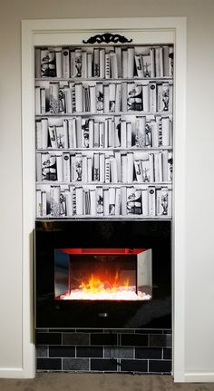Our flaming fireplace with rows of bookshelves above is it not quite what it looks like. Learn how we made it. Fake Fireplace, Fireplace Surrounds, Tile Wallpaper, Holiday Apartments, Unfinished Wood, Romantic Couples, Bookshelves, Emerald, Photo Wall