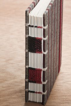 Notebook with raised cords and miniature fabric weaved along the spine!