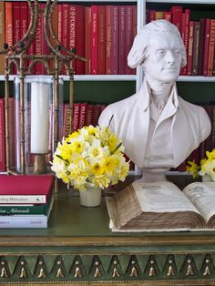 Red book spines, backs of bookshelves painted green, faux bamboo hurricane, daffodils - Carolyne Roehm