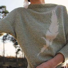 Fjærgenser. Tynn og elegant genser med en stor fjær midt på i pusete angora. Se våre mange fine garnpakker med mønster inkludert.