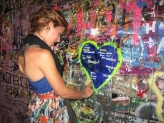 """This is a photo of Alexis in 2009. She is reading the stories and lyrics drawn onto the Old Arbat's Tsoi Wall. The fan wall is maintained in honour of Kino rockstar Viktor Tsoi and his tragic death in 1990."" (Photo by Alexis Zimberg)"