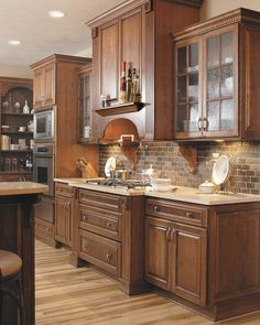 A central element of the kitchen is the soaring range hood flanked by fluted end panel boxes. Note how the fluting repeats on the range base, creating visual continuity. Mullion glass doors on each side of the hood provide design balance, and look great with Showplace Rough Rolled designer glass. The character maple floor, backsplash tile and quartz composite tops round out the rich interplay of textures. http://www.showplacewood.com/Gallery/002gen/114/114pages/114gal.3.html