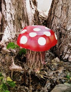 painted salad bowl placed on a tree stump looks like a mushroom