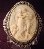 From my own collection a FABULOUS PRE BAN IVORY CAMEO OF A COURTING SCENE WITH CUPID AND LOVE BIRDS.The setting is silver not marked but tested.Has the c and t pin from around 1860.The size is 2 1/4 by 2 3/4-very large.Fine silver setting with roses.The cameo is very intricate in the man and the women with cherub and love birds. He is whispering in her ear.I have never seen another like this