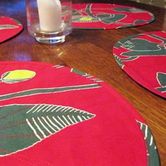 """These striking Marimekko placemats will add the """"wow factor"""" to your Christmas table setting! The combination of red, green and white in this screen print is stunning.   The """"Irmeli"""" print is a bold painted pattern perfect for the holiday season. The placemats are machine quilted to add texture and pattern, and are reversible – the """"Irmeli"""" print is used on both sides."""