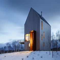 Plates of weathering steel frame the doorway to this timber-clad home, designed by Design Base 8 and Omar Gandhi for a remote site on Canada's Cape Breton