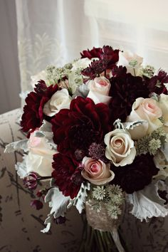 Stunning burgundy, blush and champagne wedding bouquet. Burgundy dahlias, blush roses, cream roses and dusty miller with sequin champagne wrap.