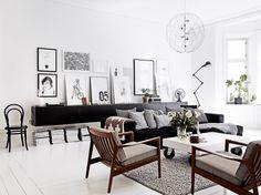 Vardagsrum i skandinavisk stil med tavelvägg och vägghängd förvaring.
