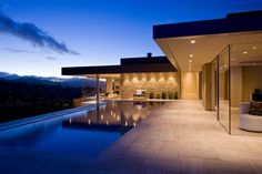 La terrasse avec la piscine de cette superbe maison de luxe joliment éclairée dans la nuit