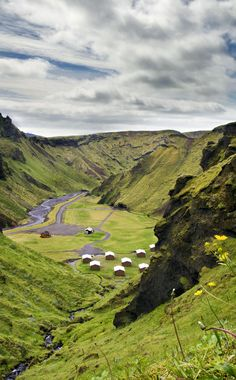 Near the village of Vik, south Iceland  lies a small enclosed canyon, sheltered on all sides by steep, moss-covered vertical mountains. The floor of the canyon is a grassy plain, about the size of an American football field, which serves as a camping site. A  little freshwater stream trickles though the camping site and in front of the houses and the surrounding landscape is spectacular. A hiker´s paradise.