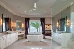 His and her vanities rest opposite each other in this luxurious master bath with a spacious walk-in shower and freestanding soaking tub overlooking the ocean. An adjoining makeup vanity and cushioned seating area add to the elegant design.