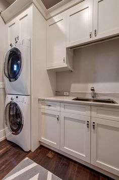 Laundry room white cabinet paint color is Sherwin Williams SW 6385 Dover White. Laundry Room gray wall paint color is Sherwin Williams Agreeable Gray. Calusa Construction, Inc.