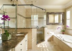Dark Emperador marble countertops contrast with Ivory Classic travertine tile in the master bathroom.