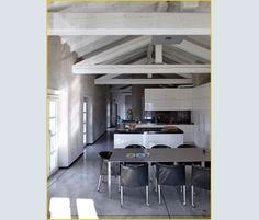 In continuità con la zona living, la CUCINA è stata realizzata su disegno del proprietario. LAMPADE A SOFFITTO grigio antracite di Viabizzuno. Le travi a vista sono quelle originali