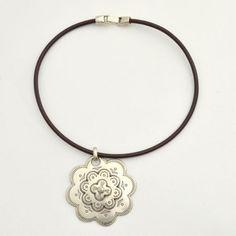 Colgante de flor en flor, con abalorio zamak en forma de flor y tira de cuero ancha en color marrón. PRECIO: 12 €