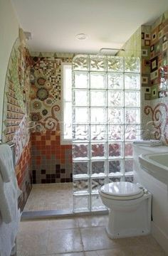Glass brick shower division and mosaic tiled wall in Cambridgeshire bathroom UK