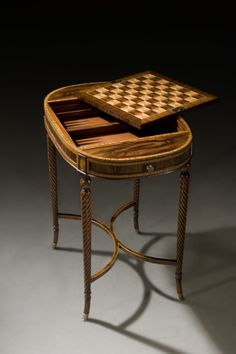 After Dinner at the Manse   A wild rosewood and satinwood banded tray top table, the oval tray top with a zigzag veneered gallery and brass handles, with a sycamore, rosewood and satinwood chess and backgammon board below and a further leather inlaid backgammon well below, on spiral turned legs joined by an 'X' stretcher, with fine brass feet.  By Theodore Alexander