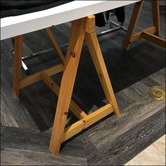 An interesting design tension is created by these Natural-Wood Sawhorse Table-Stands in stark contrast with the gleaming white Formica Table Top. Saw Horse Table, Simple Designs, Cool Designs, Formica Table, Retail Fixtures, Natural Wood, Studio, Furniture, Home Decor