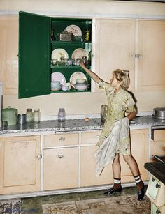1940.Daughter of Mormon farmer putting away dishes in kitchen cabinet : Colorization