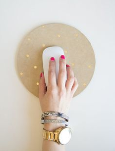 Transform a boring mouse pad into a pretty desk accessory by adding gold polka dots.  Source: Lovely Indeed