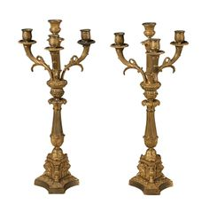 """A pair of Empire bronze core candelabra with tripartite griffon bases.  Designed by Percier and Fontaine. CIRCA: 1820 DIMENSIONS: 21"""" h x 9"""" w PRICE: $8,500"""