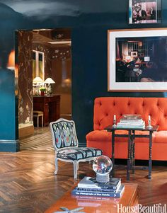 The fabric on the Louis XV-style slipper chair ties in the contrasting dark blue walls and bright orange sofa in a Manhattan living room. Design: Miles Redd