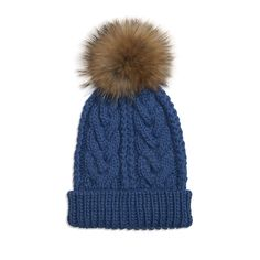 Somerville Cable Knit Hat - Denim: A gorgeous hand-knitted cable-knit raccoon fur pom pom bobble hat. Ideal for keeping your head warm and protected on chilly autumn, winter and spring days. Available in a range of colours with raccoon fur pom pom.   The cable knit hat is made from hand knitted super soft acrylic.   One size