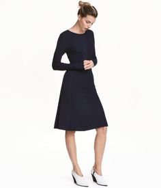 Dark blue. Knee-length dress in rib-knit fabric with flat-knit sections. Long sleeves and flared skirt. Unlined.