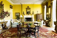 Yellow Country House Living Room with antique furniture and red rug at Faringdon House. Discover living room design ideas and inspiration in House & Garden.