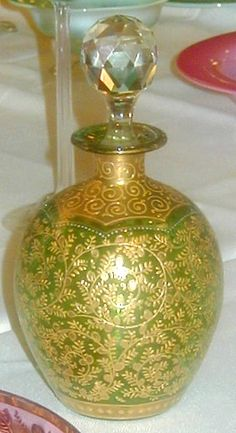 A Moser green cologne bottle with overall gold scrolling and faceted stopper. Czechoslovakia, circa 1893-2005