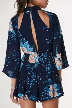 Mock neck printed romper with floral prints and textured finish. Cropped bell sleeves with cut outs in front and back.