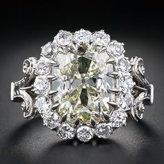An impressive and entrancing light yellow antique cushion-cut diamond, weighing 4.14 carats, glistens and glows from within a sparkling halo of bright-white European-cut diamonds in this extravagantly detailed handmade mounting created in platinum to emulate a traditional late-nineteenth/early-twentieth century counterpart. Scrolled shoulders and an all around hand-engraved ring shank complete this dynamic and dazzling diamond ring.    This is a big one!