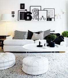 Patterned throw pillows against a white sofa. Picture frames above accent the white walls.