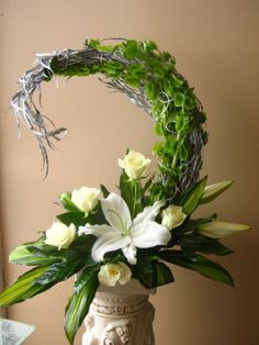 White Casablanca lilies and roses along with Aspidistra leaves - Hogarth curved arrangement
