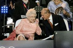 Queen Elizabeth II removing one of her earplugs to hear what Prince Philip is saying. They are so cute together.