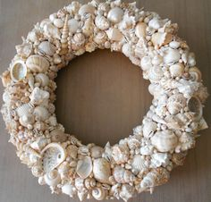 A stunning handmade seashell wreath. Each item is unique, made from natural seashells. A mixture of light brown, beige and cream / white