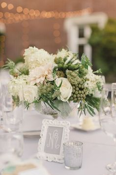 The neutral tones of the flowers—blush pink, ivory and moss green—look stunning against the light gray linens. Floral design by Violetta.