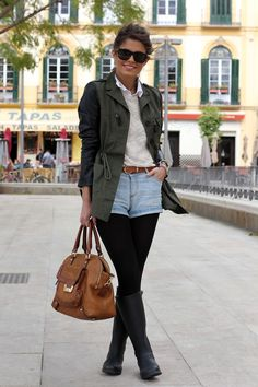 layer a white button down underneath a sparkly sweater and wear denim shorts, black tights, black boots, and an olive jacket