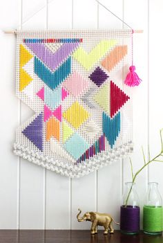 Woven colourful, geometric pattern banner, unique shape with neon pink tassel.